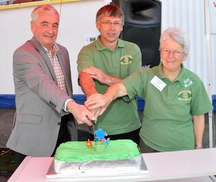 Former Masterton Mayor Bob Francis (left) cuts the cake at the Wairarapa Green Dollar Exchange's 20th anniversary.